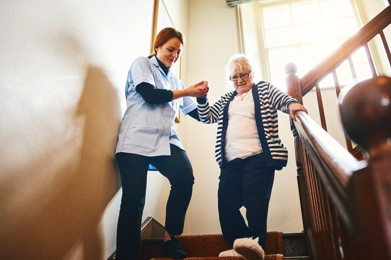 Young female caregiver helping senior woman walking down stairs at home